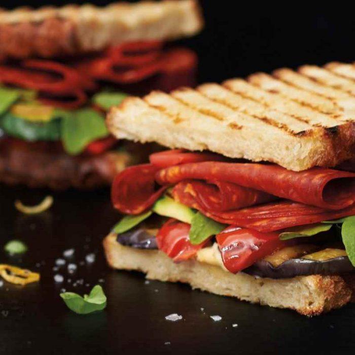 Chorizo sandwich with grilled vegetables, fresh basil, lemon hummus and arugula